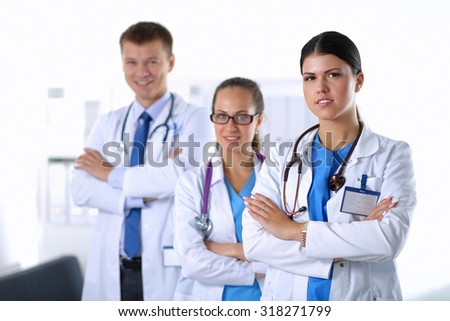 Portrait of a smiling medical team standing with their hands crossed. - stock photo