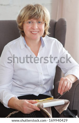 Portrait of a smiling middle age woman stitching at home