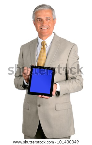 Portrait of a smiling middle aged businessman in a light suit with a tablet computer with display on blue screen. Three quarters view over a white background. - stock photo