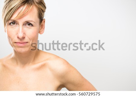Portrait of a smiling middle aged caucasian woman against grey background (shallow DOF; color toned image)