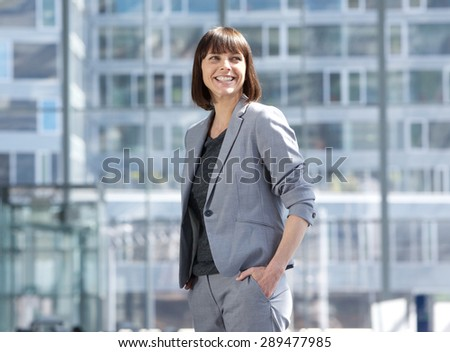Portrait of a smiling modern business woman standing in the city - stock photo
