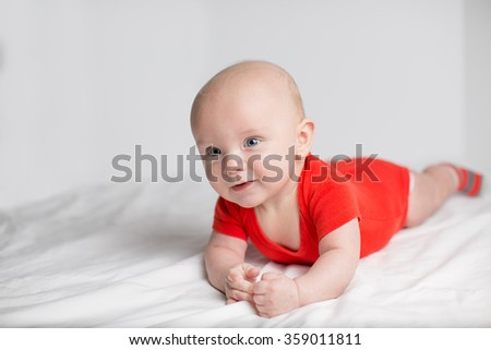 Portrait of a smiling 5 months baby boy in a red onesie lying down on a white blanket, looking aside