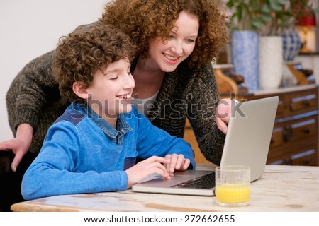 Portrait of a smiling mother and child using laptop at home  - stock photo