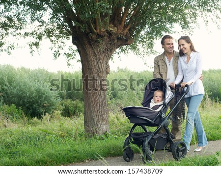 Portrait of a smiling mother and father walking outdoors and pushing baby in pram