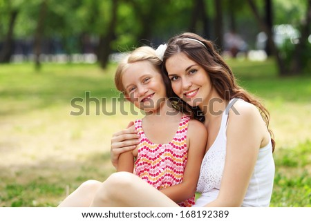 Portrait of a smiling mother and teenage daughter in summer park - stock photo