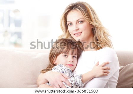 Portrait of a smiling mother hugging her adorable daughter while sitting on sofa at home.  - stock photo