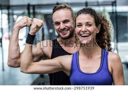 Portrait of a smiling muscular couple flexing biceps - stock photo