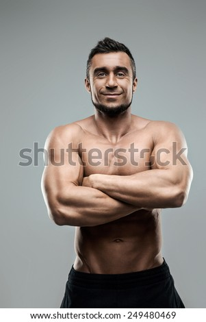 Portrait of a smiling muscular man standing with arms folded - stock photo
