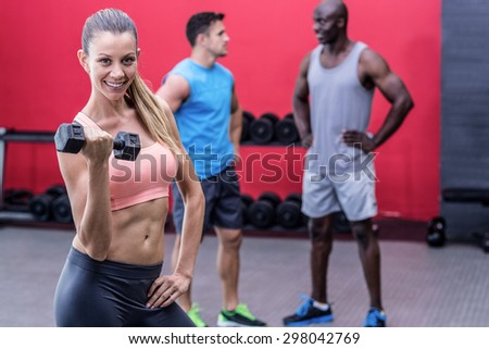 Portrait of a smiling muscular woman lifting a dumbbell