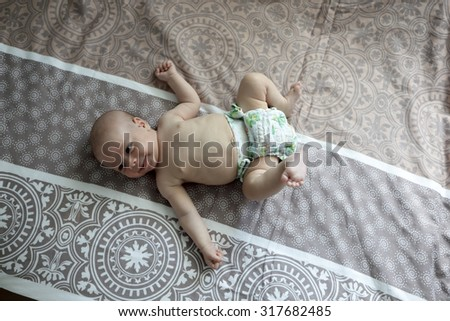 Portrait of a smiling newborn baby on a bed - stock photo