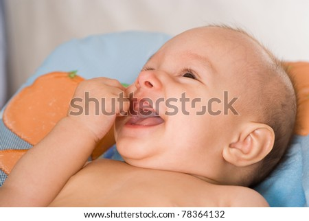 portrait of a smiling newborn on a bed