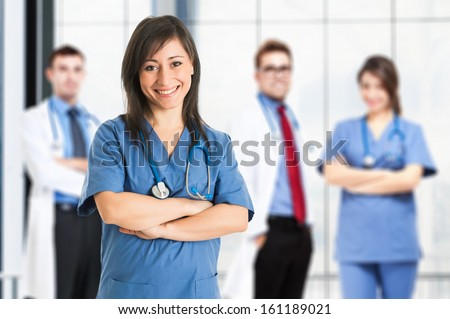 Portrait of a smiling nurse in front of her medical team