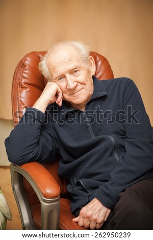 portrait of a smiling old man with a head reclined upon his hand - stock photo