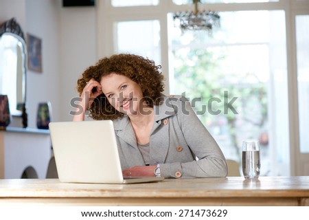 Portrait of a smiling older woman sitting at table using laptop - stock photo
