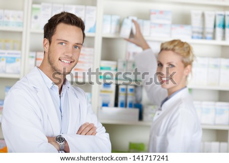 Portrait of a smiling pharmacists team smiling in front of medicines at drugstore - stock photo
