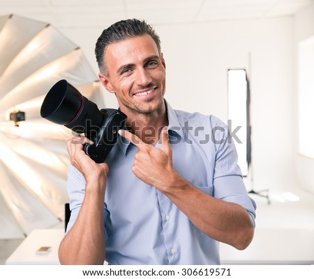 Portrait of a smiling photographer pointing finger at camera in studio - stock photo