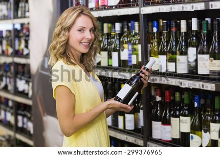 Portrait of a smiling pretty blonde woman having a wine bottle in her hands in supermarket