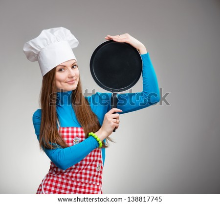 Portrait of a smiling pretty woman in chef's hat with the pan in her hands - stock photo