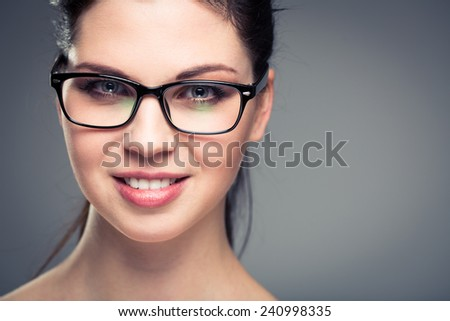 Portrait of a smiling pretty, young woman wearing glasses with copy space - studio shot, color toned - stock photo