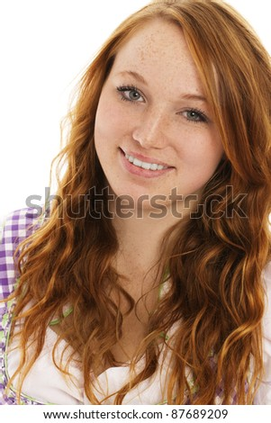 portrait of a smiling redhead woman in bavarian dress on white background - stock photo