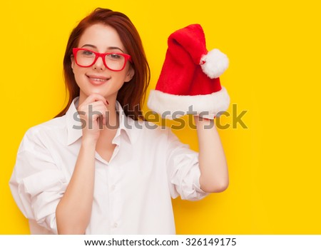 Portrait of a smiling redhead woman with Santa Claus hat on yellow background