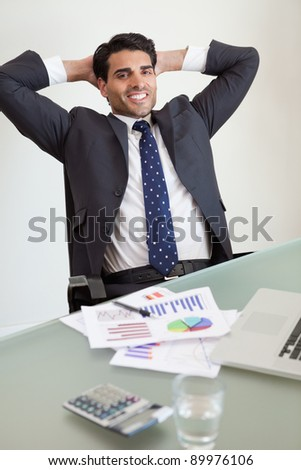 Portrait of a smiling sales person relaxing in his office