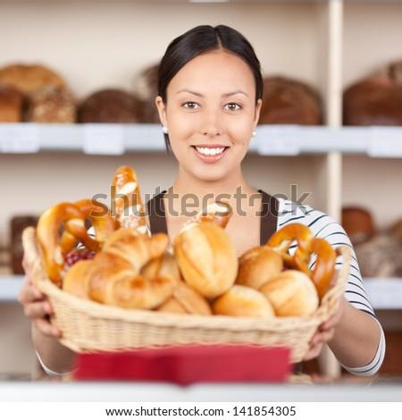 portrait of a smiling saleswoman holding breadbasket in bakery - stock photo