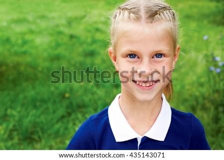 Portrait of a smiling schoolgirl in a blue school dress.  - stock photo