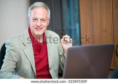 Portrait of a smiling senior businessman sitting in his office - stock photo