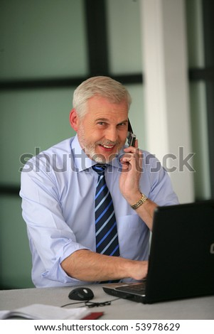 Portrait of a smiling senior businessman with a phone and a laptop computer - stock photo