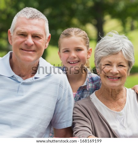 Portrait of a smiling senior couple and granddaughter at the park