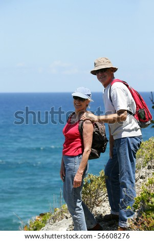 Portrait of a smiling senior couple of hikers - stock photo