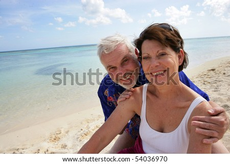 Portrait of a smiling senior couple on the beach - stock photo