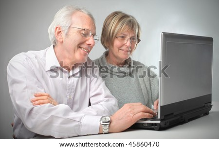 Portrait of a smiling senior couple sitting in front of a laptop - stock photo