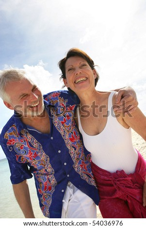 Portrait of a smiling senior couple walking on the beach - stock photo