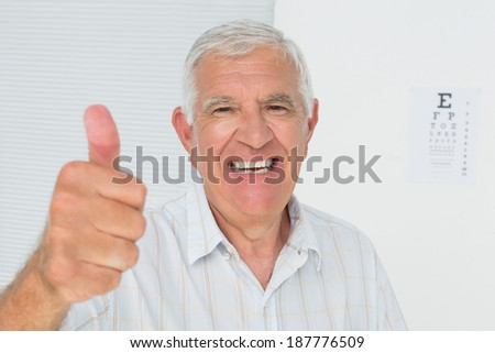 Portrait of a smiling senior man gesturing thumbs up with eye chart in the background at medical office - stock photo