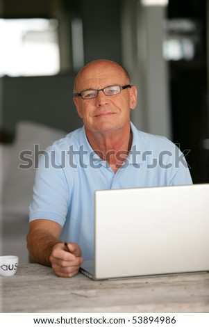 Portrait of a smiling senior man in front of a laptop computer