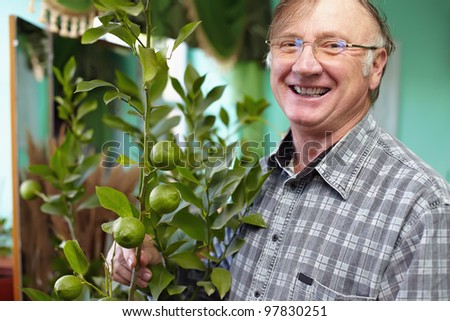 Portrait of a smiling senior man looking after houseplant lemon and proud of its growth