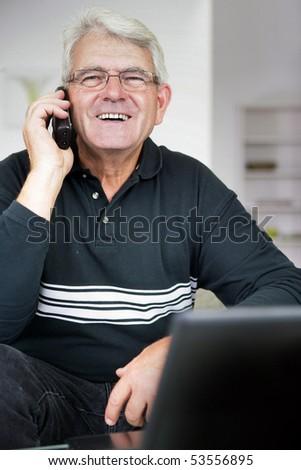 Portrait of a smiling senior man phoning - stock photo