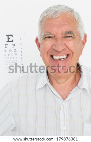 Portrait of a smiling senior man with eye chart in the background at medical office - stock photo