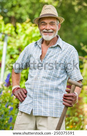 Portrait of a smiling senior with a spade in the garden - stock photo