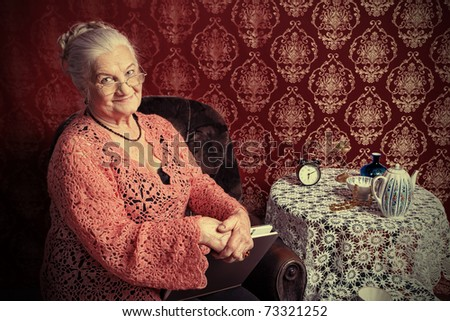 Portrait of a smiling senior woman having a rest at home. - stock photo