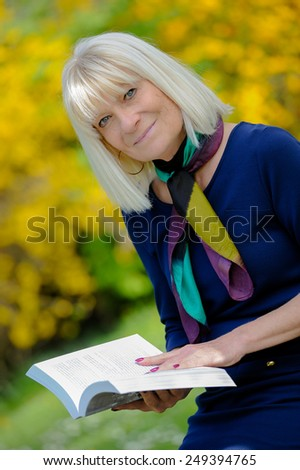 Portrait of a smiling senior woman reading a book - stock photo
