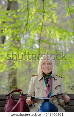 Portrait of a smiling senior woman reading a book sitting on a bench - stock photo