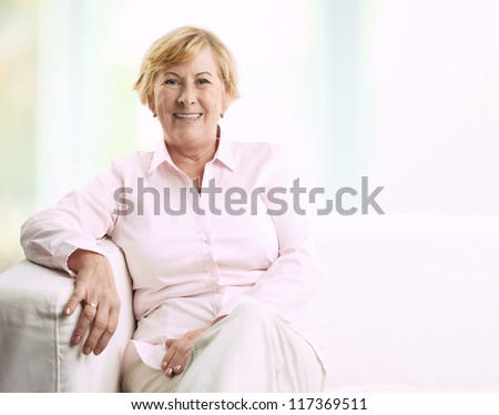 Portrait of a smiling senior woman sitting on couch at home - stock photo