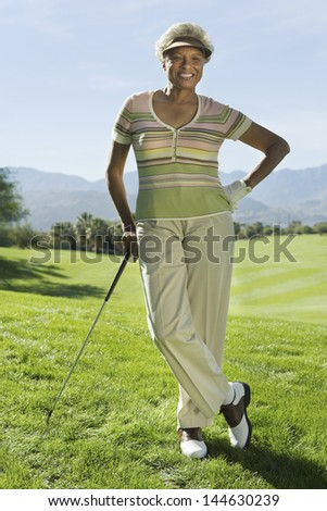 Portrait of a smiling senior woman standing on golf course - stock photo