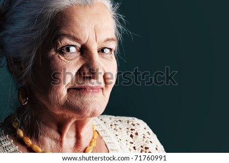 Portrait of a smiling senior woman. Studio shot over grey background. - stock photo