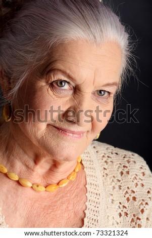 Portrait of a smiling senior woman. Studio shot over grey background. - stock photo