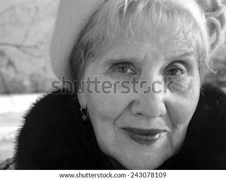 Portrait of a smiling senior woman, winter scene, outdoor shot in black and white - stock photo