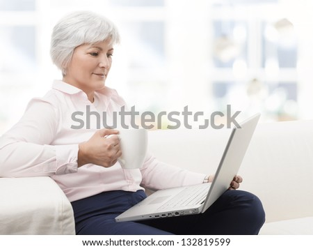 Portrait of a smiling senior woman working on laptop and drinking a cup of coffee - stock photo
